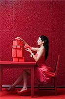 red chair - Woman in red room with gifts Stock Photo - Premium Royalty-Freenull, Code: 6114-06596307