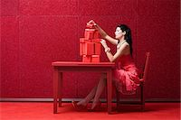 red chair - Woman in red room with gifts Stock Photo - Premium Royalty-Freenull, Code: 6114-06596312