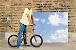 Young man on bicycle by sky backdrop Stock Photo - Premium Royalty-Free, Artist: Jodi Pudge, Code: 6114-06596492