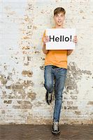 person holding sign - Teenage boy holding sign Stock Photo - Premium Royalty-Freenull, Code: 6114-06596500