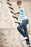 Teenage boy on a ladder Stock Photo - Premium Royalty-Free, Artist: Blend Images, Code: 6114-06596522