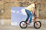 Young man on bicycle by sky backdrop Stock Photo - Premium Royalty-Free, Artist: Robert Harding Images, Code: 6114-06596539