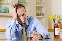 Stressed man with whisky Stock Photo - Premium Royalty-Freenull, Code: 6114-06596781