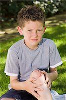 sad child sitting - Boy with a grazed knee Stock Photo - Premium Royalty-Freenull, Code: 6114-06596835