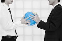 Office workers holding globe Stock Photo - Premium Royalty-Freenull, Code: 6114-06596850
