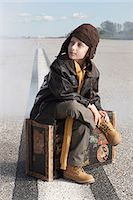 Boy sitting on suitcase on runway Stock Photo - Premium Royalty-Freenull, Code: 6114-06597104