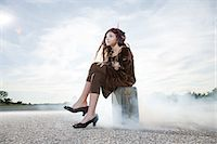 Girl sitting on suitcase Stock Photo - Premium Royalty-Freenull, Code: 6114-06597132