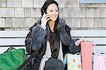 Woman on cellphone with shopping bags Stock Photo - Premium Royalty-Freenull, Code: 6114-06597822