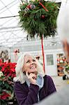 Woman looking at christmas decorations Stock Photo - Premium Royalty-Free, Artist: Blend Images, Code: 6114-06597948