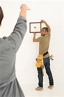 Couple hanging picture frame Stock Photo - Premium Royalty-Freenull, Code: 6114-06598025