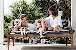 Mother and children on seat outdoors Stock Photo - Premium Royalty-Free, Artist: Blend Images, Code: 6114-06598148