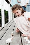 Girl playing with seashells Stock Photo - Premium Royalty-Free, Artist: Michael Eudenbach, Code: 6114-06598150