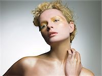 Young woman covered in gold make up Stock Photo - Premium Royalty-Freenull, Code: 6114-06598360
