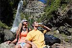 Couple having a drink by waterfall Stock Photo - Premium Royalty-Free, Artist: Westend61, Code: 6114-06598598
