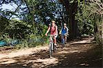 Couple cycling through forest Stock Photo - Premium Royalty-Free, Artist: CulturaRM, Code: 6114-06598620