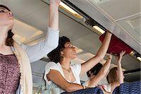 Passengers putting luggage in lockers on plane Stock Photo - Premium Royalty-Freenull, Code: 6114-06599039