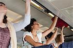 Passengers putting luggage in lockers on plane Stock Photo - Premium Royalty-Free, Artist: Albert Normandin, Code: 6114-06599039