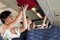 Passengers putting luggage in lockers on plane Stock Photo - Premium Royalty-Freenull, Code: 6114-06599092