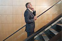 Businessman on escalator Stock Photo - Premium Royalty-Freenull, Code: 6114-06599167