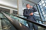 Businessman using cellphone on escalator Stock Photo - Premium Royalty-Free, Artist: Blend Images, Code: 6114-06599202