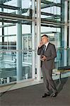 Businessman on cellphone in office Stock Photo - Premium Royalty-Free, Artist: Uwe Umstätter, Code: 6114-06599205