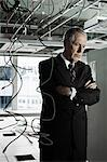 Businessman in office with cables hanging from ceiling Stock Photo - Premium Royalty-Free, Artist: Blend Images, Code: 6114-06599401