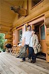 Young couple standing outside log cabin Stock Photo - Premium Royalty-Free, Artist: Blend Images, Code: 6114-06599722
