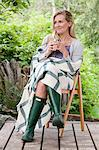 Mid adult woman sitting wearing wellington boots and shawl Stock Photo - Premium Royalty-Free, Artist: Robert Harding Images, Code: 6114-06599730