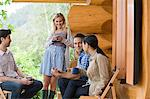 Four young people outside log cabin Stock Photo - Premium Royalty-Free, Artist: Janet Foster, Code: 6114-06599760