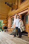 Young couple standing outside log cabin Stock Photo - Premium Royalty-Free, Artist: Robert Harding Images, Code: 6114-06599762