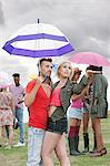 Young couple under umbrella at festival, testing for rain Stock Photo - Premium Royalty-Free, Artist: CulturaRM, Code: 6114-06599811