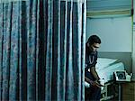 Young male doctor sitting on hospital bed Stock Photo - Premium Royalty-Free, Artist: Aflo Relax, Code: 6114-06600010