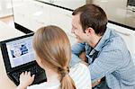 Young couple looking at insurance on laptop Stock Photo - Premium Royalty-Free, Artist: Robert Harding Images, Code: 6114-06600261