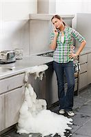 Young woman on phone with overflowing dishwasher Stock Photo - Premium Royalty-Freenull, Code: 6114-06600267
