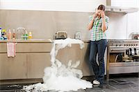 Young woman on phone with overflowing dishwasher Stock Photo - Premium Royalty-Freenull, Code: 6114-06600268