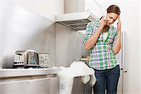 Young woman on phone with overflowing dishwasher Stock Photo - Premium Royalty-Freenull, Code: 6114-06600270