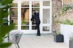 Burglar standing at patio door Stock Photo - Premium Royalty-Free, Artist: Cultura RM, Code: 6114-06600337