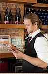 Bar manager looking at paperwork Stock Photo - Premium Royalty-Free, Artist: ableimages, Code: 6114-06600398