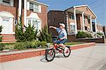 Paperboy with bike throwing newspaper Stock Photo - Premium Royalty-Freenull, Code: 6114-06600411