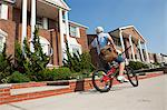 Paperboy with bike throwing newspaper Stock Photo - Premium Royalty-Freenull, Code: 6114-06600438
