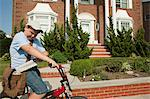 Paperboy with bike delivering newspapers Stock Photo - Premium Royalty-Free, Artist: Blend Images, Code: 6114-06600445