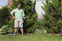 Man watering grass with hosepipe Stock Photo - Premium Royalty-Freenull, Code: 6114-06600449