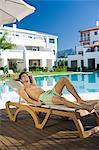 Man relaxing on sunlouger by poolside Stock Photo - Premium Royalty-Free, Artist: Westend61, Code: 6114-06600580