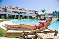Woman sunbathing on sunlounger at poolside Stock Photo - Premium Royalty-Freenull, Code: 6114-06600594