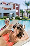 Two women sunbathing on sunloungers at poolside Stock Photo - Premium Royalty-Free, Artist: Westend61, Code: 6114-06600604