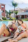 Two women sunbathing on sunloungers reading magazines Stock Photo - Premium Royalty-Free, Artist: CulturaRM, Code: 6114-06600619