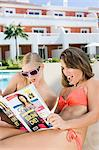 Two women sunbathing on sunloungers reading magazines Stock Photo - Premium Royalty-Free, Artist: urbanlip.com, Code: 6114-06600622