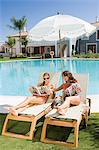 Two women sunbathing on sunloungers reading magazines Stock Photo - Premium Royalty-Free, Artist: Blend Images, Code: 6114-06600623