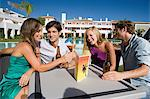 Four friends enjoying drinks on holiday Stock Photo - Premium Royalty-Free, Artist: Blend Images, Code: 6114-06600634