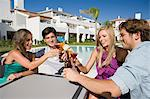 Four friends enjoying drinks on holiday Stock Photo - Premium Royalty-Free, Artist: Cultura RM, Code: 6114-06600637